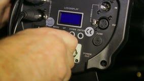 A m?o do iluminador une um fio el?trico da rede ao projetor de perfil filme