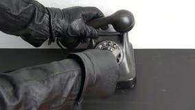 Mão do ladrão do gângster com a luva de couro preta que disca o seletor de telefone antigo com punhal do vintage filme