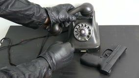 Mão do ladrão do gângster com a luva de couro preta que disca o telefone antigo filme