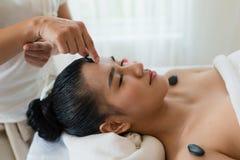 Mão do lugar do massagista da mulher a pedra na cara de uma menina Ásia Foto de Stock Royalty Free