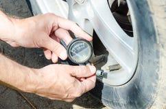 Mão do mecânico que verifica a pressão de ar no pneu com o close up do calibre imagem de stock