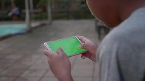 Mão do menino das crianças usando o jogo esperto do jogo do telefone em linha na tela verde que relaxa perto da piscina na noite vídeos de arquivo