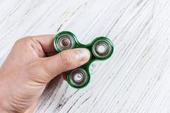 mão do menino que joga com o dispositivo do girador da inquietação Girador verde da mão, brinquedo remexendo-se da mão que gira n Fotografia de Stock Royalty Free
