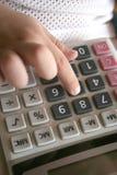 Mão do miúdo usando a calculadora fotografia de stock