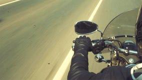 Mão do motociclista na direção da motocicleta e na estrada foto de stock