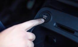 A mão do motorista empurra o botão de parada do começo do motor fotos de stock royalty free