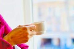 Mão do mulheres com uma xícara de café na cor branca imagens de stock royalty free