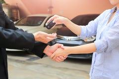 Mão do negócio que dá uma chave do comprador no carro alugado imagens de stock