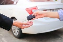 Mão do negócio que dá uma chave para o comprador ou o carro alugado fotografia de stock royalty free