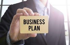 Mão do negócio que guarda o cartão com plano de negócios da mensagem Imagem de Stock