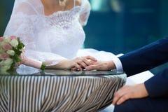 Mão do noivo da terra arrendada da noiva Imagens de Stock