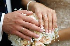 Mão do noivo e da noiva com alianças de casamento Foto de Stock