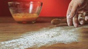 Mão do padeiro que prepara a farinha na tabela para fazer a massa o movimento lento filme