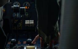 Mão do piloto do helicoter que empurra algum botão no painel de controle fotografia de stock