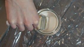 Mão do pintor que mergulha uma escova em uma cubeta com pintura branca, movimento lento video estoque
