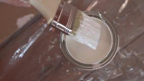 Mão do pintor que mergulha uma escova em uma cubeta com pintura branca, movimento lento filme