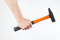 Mão do reparador com um martelo no fundo branco Fotos de Stock Royalty Free