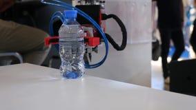 A mão do robô está guardando uma garrafa da água media Progresso tecnol?gico O braço robótico guarda uma garrafa de água filme