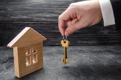 A mão do ` s do corretor de imóveis guarda as chaves à casa Casa de madeira O conceito de comprar e de vender os apartamentos imagens de stock royalty free