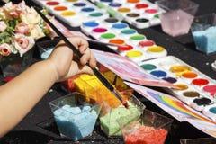 A mão do ` s da criança guarda um pincel para pintar no papel em uma oficina criativa fora em um dia ensolarado foto de stock royalty free
