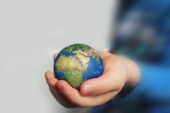 Mão do ` s da criança que guarda o globo fotografia de stock royalty free