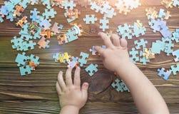 A mão do ` s da criança recolhe um enigma Imagem de Stock