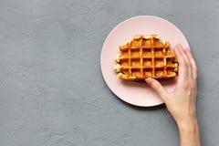A mão do ` s da jovem mulher toma um waffle belga tradicional, vista aérea De cima de, aéreo Fundo concreto fotografia de stock royalty free