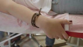 A mão do ` s da menina com bracelete de couro guarda o sofá ao ser tattooed Movimento lento video estoque