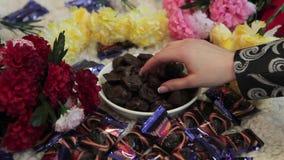 A mão do ` s da menina toma uma parte de doces ou de chocolate da placa branca O ` s da mulher entrega a tomada do chocolate doce filme