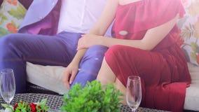 A mão do ` s da mulher afaga um pé do ` s do homem Um homem e uma mulher relaxam e bebem o champanhe filme