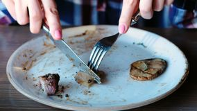 A mão do ` s da mulher do close up que corta a parte de carne de porco cozinhou nos carvões com batatas, molho e verdes na placa video estoque
