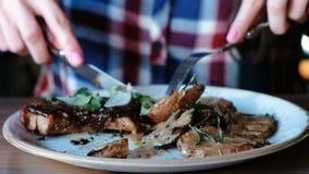 A mão do ` s da mulher do close up que corta a parte de carne de porco cozinhou nos carvões com batatas, molho e verdes na placa  vídeos de arquivo