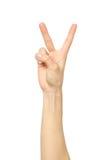 Mão do ` s da mulher com dois dedos acima no símbolo da paz ou da vitória foto de stock