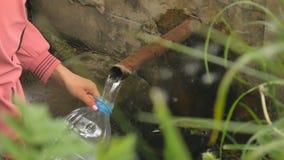 A mão do ` s da mulher derrama a água de mola natural na garrafa video estoque
