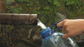 A mão do ` s da mulher derrama a água de mola natural na garrafa vídeos de arquivo