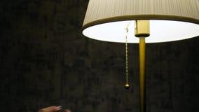 A mão do ` s da mulher desliga a lâmpada filme
