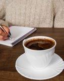 Mão do ` s da mulher na escrita da camiseta no bloco de notas na mesa Xícara de café Fotografia de Stock Royalty Free