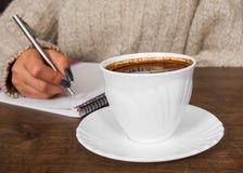 Mão do ` s da mulher na escrita da camiseta no bloco de notas na mesa Xícara de café Fotografia de Stock
