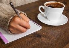 Mão do ` s da mulher na escrita da camiseta no bloco de notas na mesa Xícara de café Fotos de Stock Royalty Free