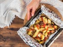 A mão do ` s da mulher põe sobre a tabela cozida em batatas da folha com carne Batatas assadas na folha na folha de cozimento Vis Fotografia de Stock Royalty Free