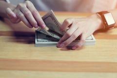 Mão do ` s da mulher que conta o dinheiro 100 dólares O conceito da despesa pelo dinheiro Fotos de Stock Royalty Free