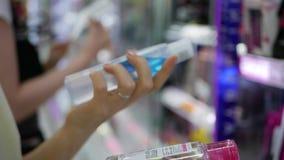 Mão do ` s da mulher que escolhe e que compra um removedor líquido da composição Uma mulher escolhe uma loção para o cuidado e os video estoque