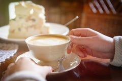 Mão do ` s da mulher que guarda o copo do cappuccino no café fotografia de stock