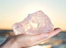 Mão do ` s da mulher que guarda o pedaço áspero de Rose Quartz da categoria da gema de Madagáscar imagem de stock