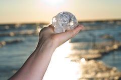 A mão do ` s da mulher que guarda o quartzo cinzelou estrangeiro maia alongado Crystal Skull no nascer do sol foto de stock royalty free