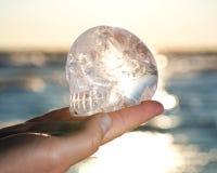 A mão do ` s da mulher que guarda o quartzo claro cinzelou Crystal Skull no nascer do sol foto de stock