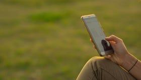 Mão do ` s da mulher que guarda o telefone celular Imagem de Stock