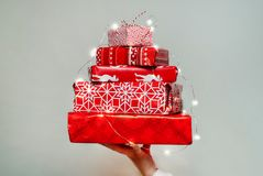 Mão do ` s da mulher que guarda uma pilha de presentes agradavelmente embalados do Natal no fundo branco Fotos de Stock Royalty Free