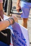 A mão do ` s da mulher que mantém o sinal do protesto em professores contra armas reagrupa com o homem borrado com telefone celul fotografia de stock