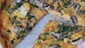 A mão do ` s da mulher toma a parte de verdes redondos do withwith da pizza, de galinha, de cogumelos e de queijo dobro video estoque